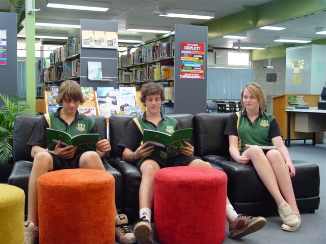 students on coach reading in resource centre